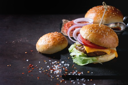 Fresh homemade burger on black slate and raw cutlet and sliced onion, served with sea salt and pepper over dark background.