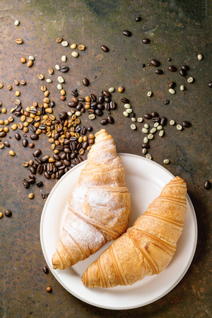 unroasted: Plate with two fresh baked croissants with heap od roasted and  unroasted coffee beans over rusty metal background
