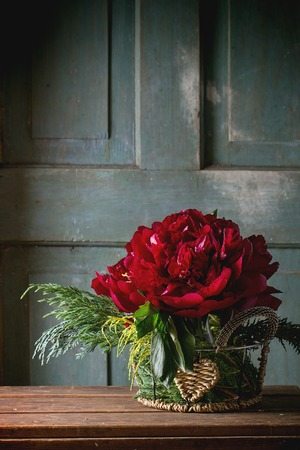 pion: Bouquet with big burgundy peonies and green bunches of thuja in vintage vase over wooden table. Dark rustic atmosphere Stock Photo