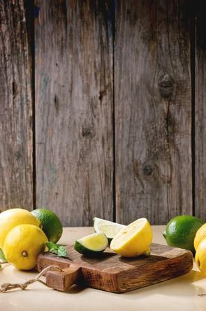 cut: Heap of whole and sliced lemons and limes on little wooden cutting board over wooden background. Rustic sun light.