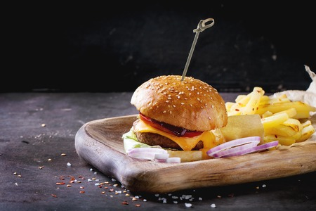 Wooden plate with fresh homemade burger and grilled potatoes over dark background.