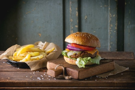 classic burger: Fresh homemade burger on little cutting board with grilled potatoes, served with ketchup sauce and sea salt over wooden table with gray wooden background. Dark rustic style.