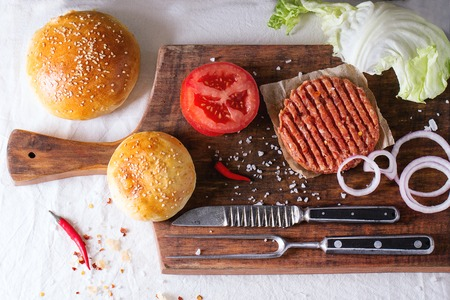 Ingredients for making homemade burger on wooden cutting board, served with meat fork and knife over White tablecloth. Dark rustic style. Top view