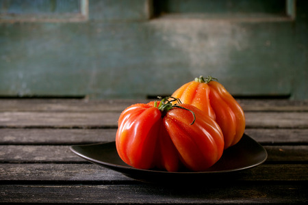 raf: Two big red tomatoes RAF on plate over old wooden table. Dark rustic atmosphere