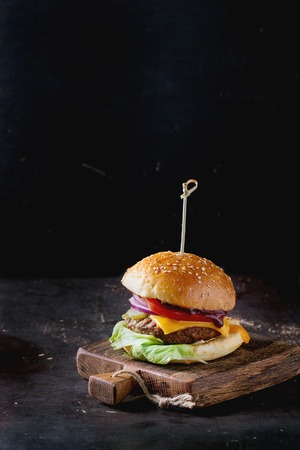 Fresh homemade burger on little wooden cutting board over dark background. Archivio Fotografico