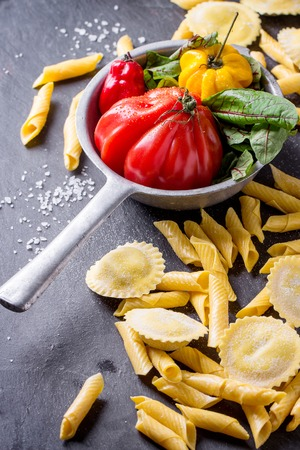 yellow flour: Homemade ravioli and garganelli pasta with flour and vintage colander with tomato RAF, salad leaves and yellow chili pepper over black slate background.