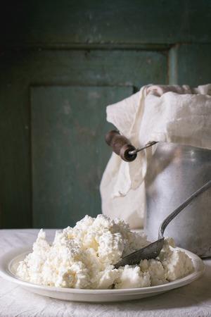 casa de campo: Plato de queso cottage casero, servido con pan de cosecha de aluminio y agua-can en el mantel blanco con turquesa fondo de madera. Ambiente rústico oscuro.