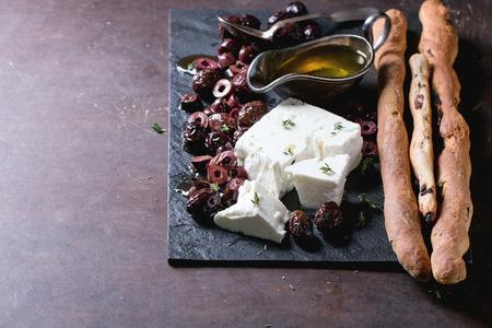 tranches de pain: Entières et tranchées olives noires et bloc de fromage feta avec de l'huile d'olive et de la maison des bâtonnets de pain de grissini sur l'ardoise noire sur fond sombre Banque d'images
