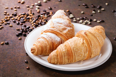decaffeinated: Plate with two fresh baked croissants with heap od roasted and  unroasted coffee beans over rusty metal background.