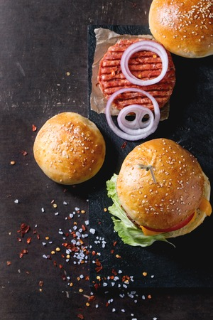 beef burger: Fresh homemade burger on black slate and raw cutlet and sliced onion, served with sea salt and pepper over dark background. Selective focus. Top view Stock Photo