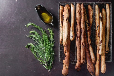 comiendo pan: Palitos de pan grisines frescas horneados caseros en caja de rejilla de metal de la vendimia con el aceite de oliva y hierbas de romero y tomillo sobre superficie oscura. Vista superior. Foto de archivo
