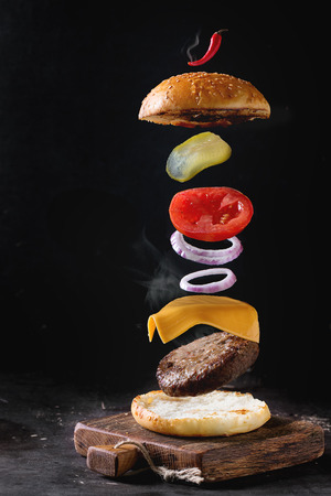 classic burger: Flying ingredients for homemade burger on little wooden cutting board over dark background. Stock Photo