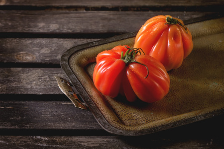 raf: Two big red tomatoes RAF on vintage tray over old wooden table. Dark rustic atmosphere