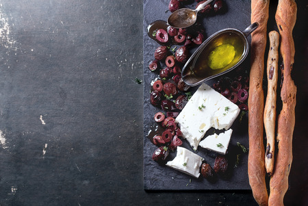 Whole and sliced black olives and block of feta cheese with olive oil and homemade grissini bread sticks on black slate over dark background. Top view