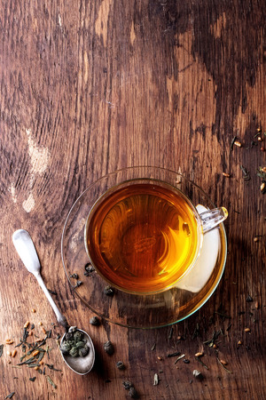 dry leaves: Glass cup of hot tea with dry green tea leaves, vintage spoon and sugar. Rustic wooden backgtound. Top view. With copy space on top