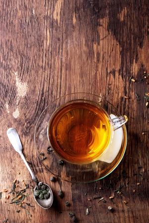 hojas secas: Taza de cristal de té caliente con secas hojas de té verde, cuchara y el azúcar de la vendimia. Backgtound madera rústica. Vista superior. Con copia espacio en la parte superior
