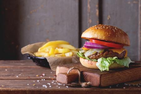 Hambúrguer caseiro fresco na pequena placa de corte com batatas grelhadas, servido com molho de ketchup e sal do mar sobre a mesa de madeira com fundo cinza de madeira. Estilo rústico escuro.
