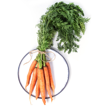 Plate with bundle of carrots over white background. Top view