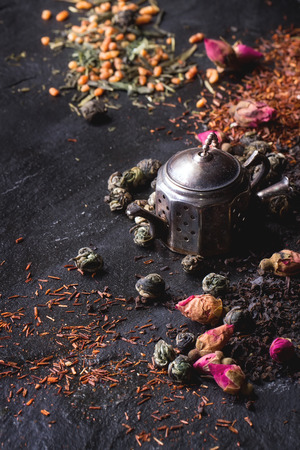 Assortment of dry tea with tea strainer as small teapot. Green tea, black tae, green tea with rice, rooibos, dry rose buds. Black textured slate background