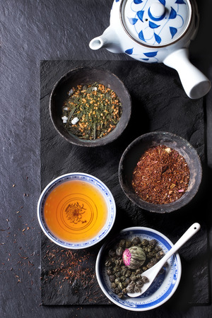 Assortment of dry tea, cup of hot tea and teapot. Green tea, black tae, green tea with rice, rooibos, dry rose buds in porcelan and old metal chinese bowls. Black textured slate background. Top view. Stockfoto