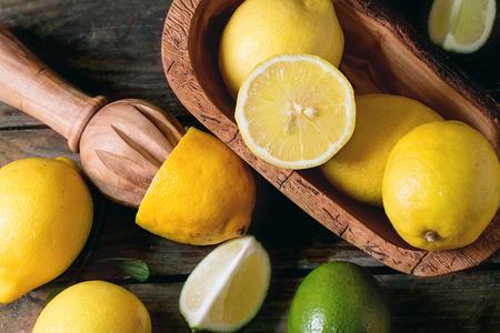citricos: Mont�n de conjunto y en rodajas los limones y limas en un taz�n de madera de olivo y exprimidor de c�tricos sobre fondo de madera. Vista superior