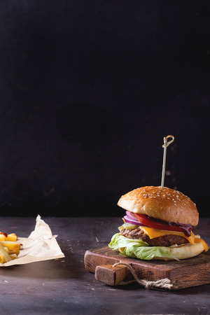 Hamburguesa casera fresca en pequeña tabla para cortar madera y patatas a la parrilla sobre fondo oscuro
