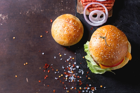 Fresh homemade burger on black slate and raw cutlet and sliced onion, served with sea salt and pepper over dark background