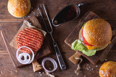 classic burger: Fresh homemade burger on little cutting board and raw cutlet and sliced onion, served with ketchup sauce and meat fork over wooden table Stock Photo