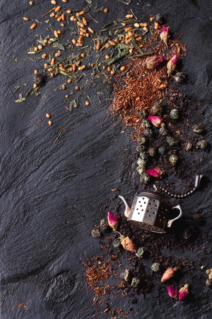 Assortment of dry tea with tea strainer as small teapot. Green tea, black tae, green tea with rice, rooibos, dry rose buds. Black textured slate background. Top view. With copy space on left. Standard-Bild
