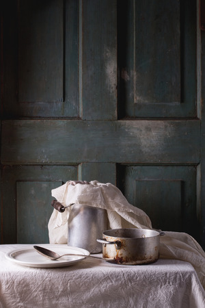 kitchenware: Rustic kitchenware vintage aluminum pan, milk water-can and white ceramic plate on white tablecloth with turquoise wooden background. Dark rustic atmosphere. Stock Photo
