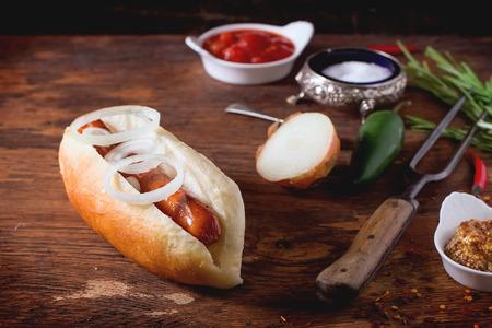 perro comiendo: Perro caliente hecho en casa con ingredientes mostaza, salsa de tomate, cebolla, pimienta, romero. En la mesa de madera con un tenedor y cuchara de carne. Foto de archivo