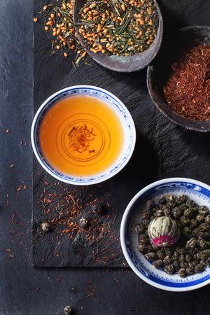 Assortiment de thé sec et une tasse de thé chaud. Le thé vert, tae noir, thé vert avec du riz, rooibos, sèche bourgeons rose dans des bols chinois métalliques Porcelán et vieux. Noir texturé fond d'ardoise. Vue d'en haut. Banque d'images - 42284446