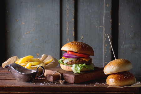 Fresh homemade burger on little cutting board with grilled potatoes, served with ketchup sauce and sea salt over wooden table with gray wooden background Stok Fotoğraf - 42283701