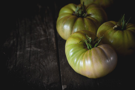 raf: Green unripe big RAF tomatoes over old wooden table. Dark rustic style. Natural day light. With copy space on left