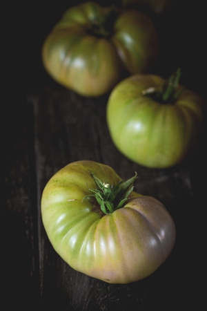 raf: Green unripe big RAF tomatoes over old wooden table. Dark rustic style. Natural day light