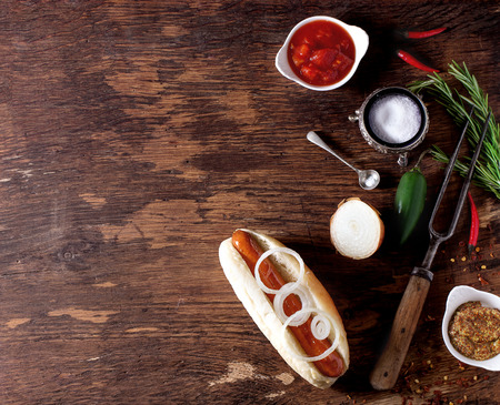 hot sauce: Homemade hot dog with ingredients mustard, tomato sauce, onion, chili pepper, rosemary. On wooden table with meat fork and spoon. Frame with copy space on left. Top view. Stock Photo