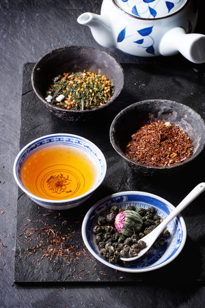 rooibos tea: Assortment of dry tea, cup of hot tea and teapot. Green tea, black tae, green tea with rice, rooibos, dry rose buds in porcelan and old metal chinese bowls. Black textured slate background.