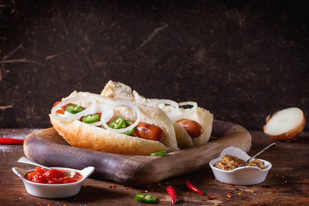 hotdog sandwiches: Homemade hot dogs on wooden plate with ingredients mustard, tomato sauce, onion, pepper, rosemary on wooden table. Dark rustic style Stock Photo