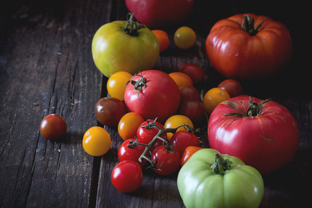 raf: Assortment of big RAF red and green and cherry tomatoes red, yellow and orange over old wooden table. Dark rustic style. Day light.