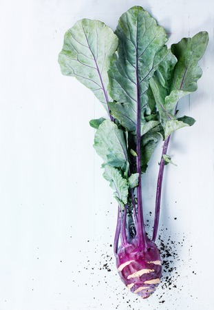 green and purple vegetables: Purple kohlrabi with tops over light blue wooden background. Top view. With copyspace on left