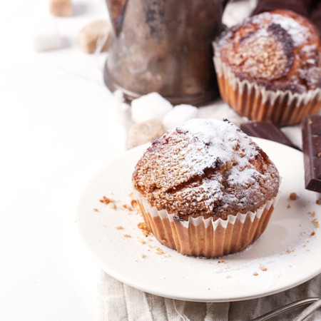 teapot: Homemade muffins with powdered sugar and vintage teapot over white. Square image with selective focus Stock Photo