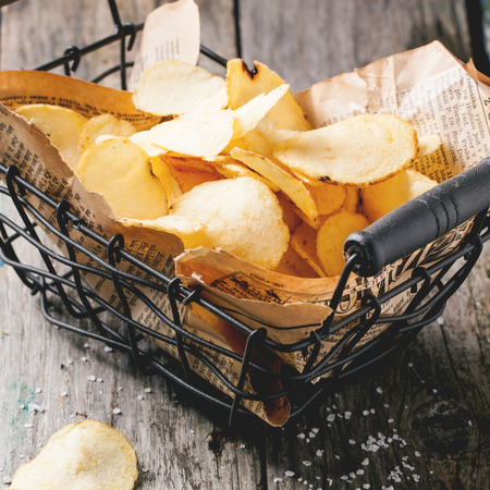Basket with potato chips with sea salt over old wooden table. Square image with selective focus