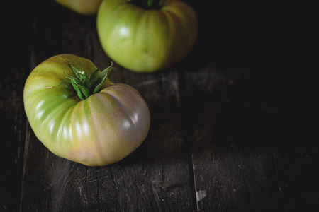 raf: Green unripe big RAF tomatoes over old wooden table. Dark rustic style. Natural day light. With copy space on right