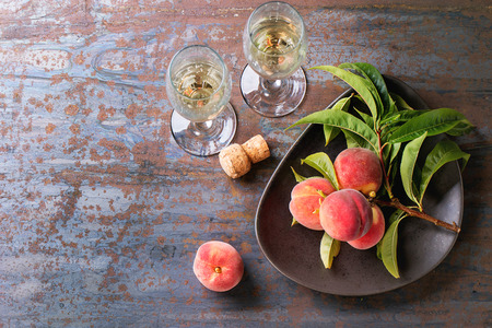 champagne glass: Peaches on branch with leaves in brown ceramic plate and two glass of champagne with cork over old metal background. Top view. Stock Photo