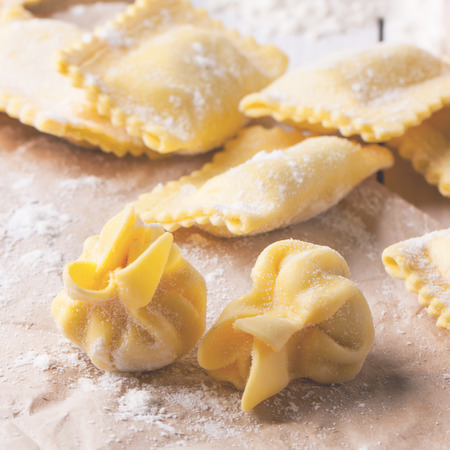 perle: Close up of homemade pasta ravioli and perle on table with flour. Square image with selective focus