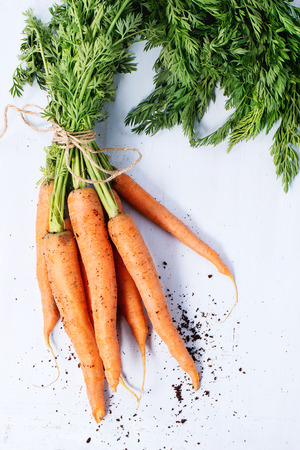carrots: Bundle of carrots with soil over light blue wooden background. Top view Stock Photo