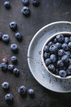 background summer: Cup of blueberries at black surface. Top view. Stock Photo