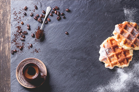 coffee spoon: White plate with homemade belgian waffles with sugar powder, ceramic cup of coffee, teaspoon and coffee beans.