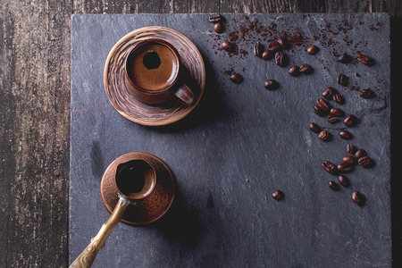 cezve: Brown ceramic cup of coffee, old copper cezve and coffee beans.