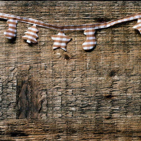 textile image: Christmas background with textile garland on wood. Square image